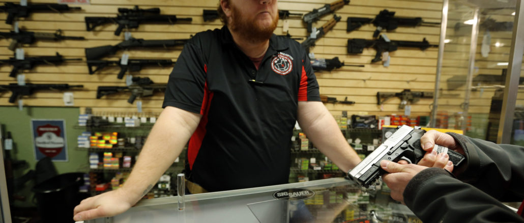 Metro Shooting Supplies' employee Chris Cox speaks to a customer about the purchase of a 9mm handgun in Bridgeton, Missouri, November 13, 2014. The store has reported an increase in gun sales as the area waits for a grand jury to reach a decision this month on whether to indict Darren Wilson, the white police officer who shot and killed the 18-year-old Mike Brown, who was black, on Aug. 9 in the St. Louis suburb of Ferguson. REUTERS/Jim Young  (UNITED STATES - Tags: CRIME LAW CIVIL UNREST POLITICS) - RTR4E2I1