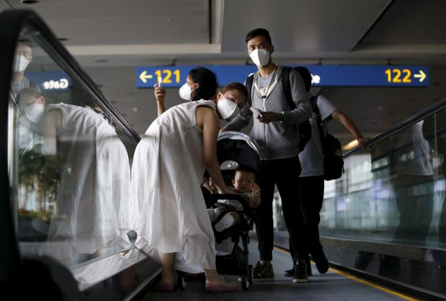 Passengers wearing masks to prevent contracting Middle East Respiratory Syndrome (MERS) ride on a travelator upon arrival at Incheon International Airport in Incheon, South Korea, June 2, 2015. REUTERS/Kim Hong-Ji