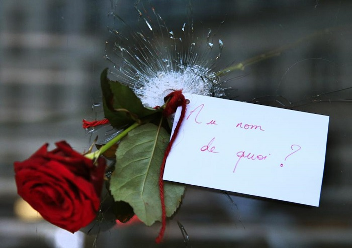 A+rose+placed+in+a+bullet+hole+in+a+restaurant+window+the+day+after+a+series+of+deadly+attacks+in+Paris+%2C+November+14%2C+2015.+The+note+reads+%22In+the+Name+of+What%3F%22+REUTERS%2FPascal+Rossignol