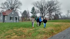 A portion of our student group is staying warm as they walk through the chilly 39 degree rain past the 1930s Sears model  house.