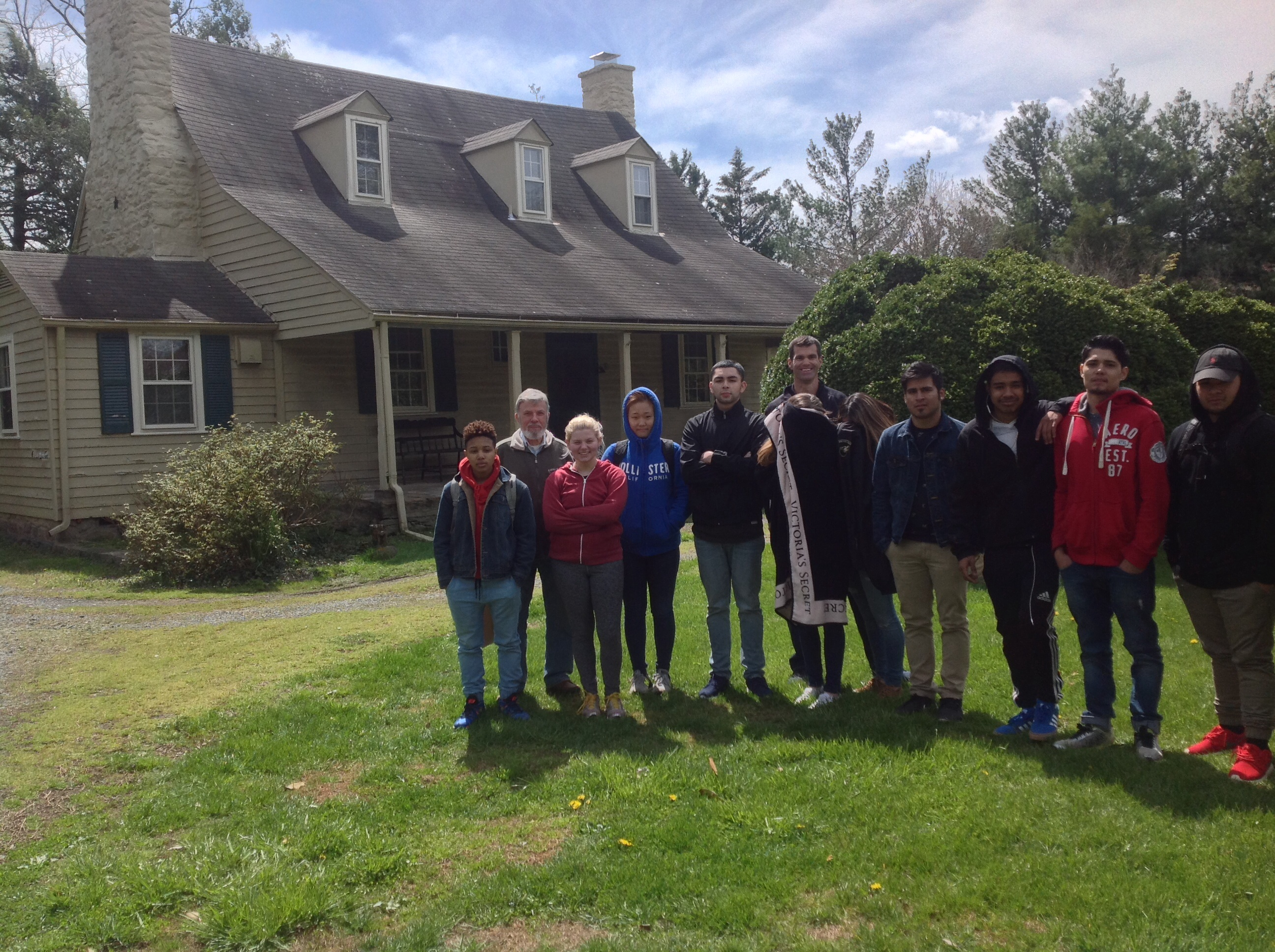 A group of students stands with the Professor in front of his historic home in the Mt. Gilead section of the historic district of Centreville, VA