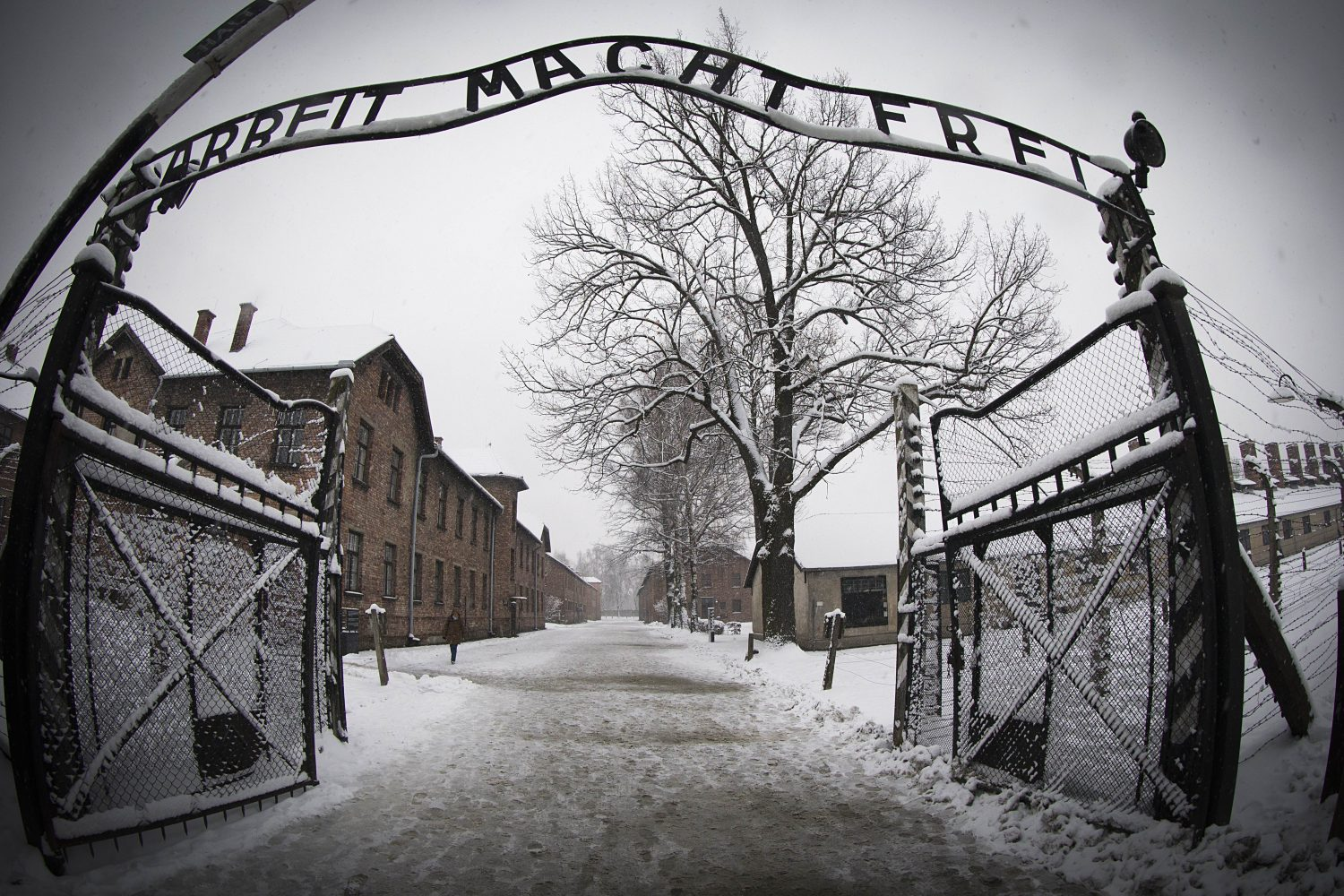 TOPSHOTS A woman walks through snow near the entrance to the former Nazi concentration camp Auschwitz-Birkenau with the lettering 'Arbeit macht frei' ('Work makes you free') in Oswiecim, Poland on January 25, 2015, days before the 70th anniversary of the liberation of the camp by Russian forces. AFP PHOTO / JOEL SAGET