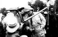 "TR examines a gun before presenting it to Chief Okawahki in ""TR in Africa"" (1909)."