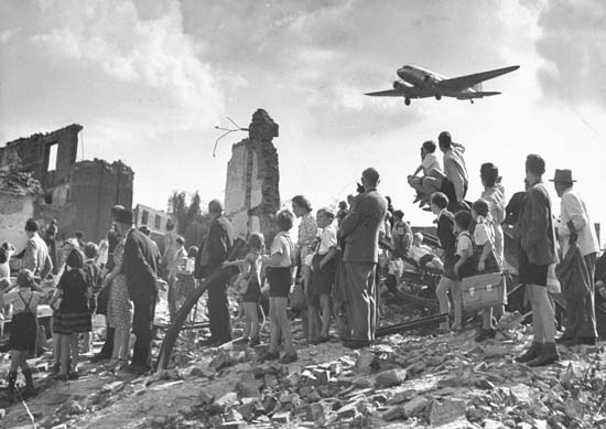 Tattered group of Berliners standing in ruins of building at the edge of Tempelhof Airfield, looking up at a C-47 cargo plane bringing them food during the Berlin airlift to break blockade of overland routes imposed by Soviet cordon.  (Photo by Walter Sanders//Time Life Pictures/Getty Images)