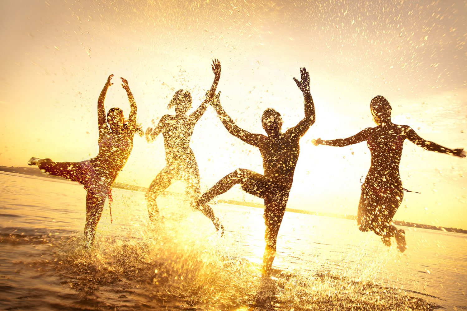 group+of+happy+young+people+dancing+and+spraying+at+the+beach+on++beautiful+summer+sunset